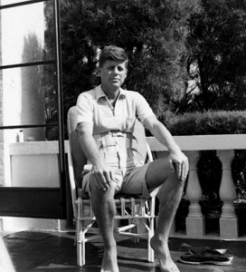 Senator John F. Kennedy wears a back brace as he sits on the patio in Palm Beach, Florida.