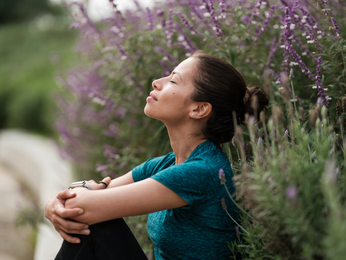 Woman, seated, practicing mindfulness next to some flowers