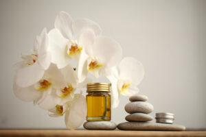arrangement of orchid flowers, massage stones, CBD oil