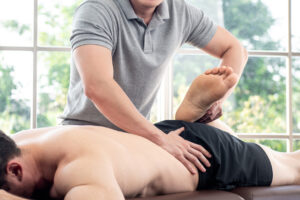 Physical therapist performing assisted stretching of male client's right leg